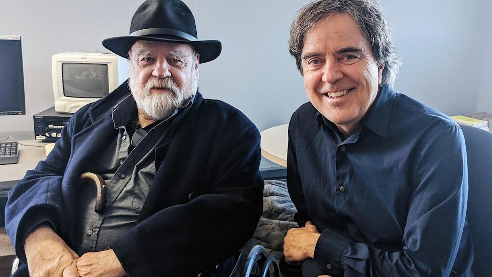 Assis dans un bureau, deux hommes sourient à la caméra.