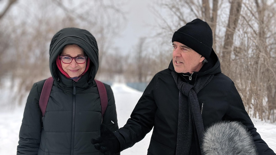 Une femme sourit tandis qu'un homme lui parle; les deux sont à l'extérieur en hiver.