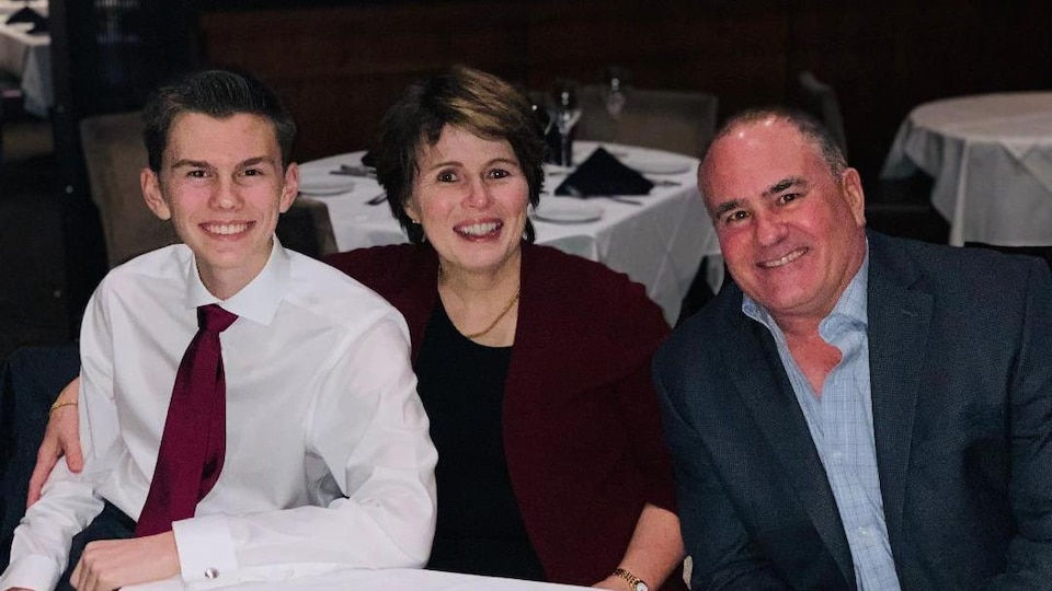 Un jeune homme, une dame et un homme assis autour d'une table.