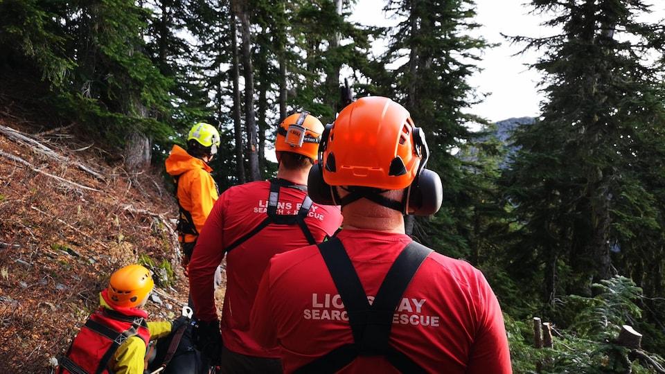Des hommes et des femmes dans une montagne. Ils sont en train de sauver une personne.