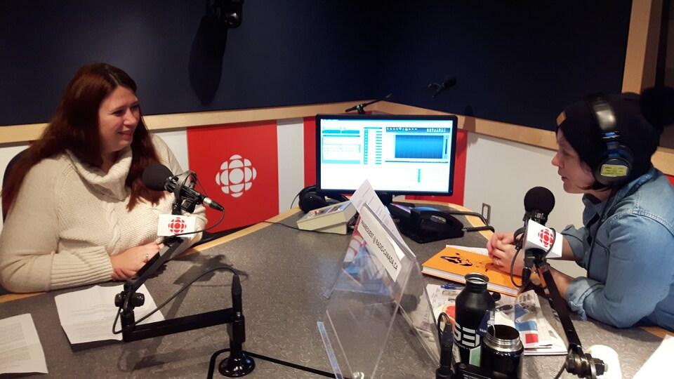 Deux femmes sont assises, devant un micro, dans un studio de radio.