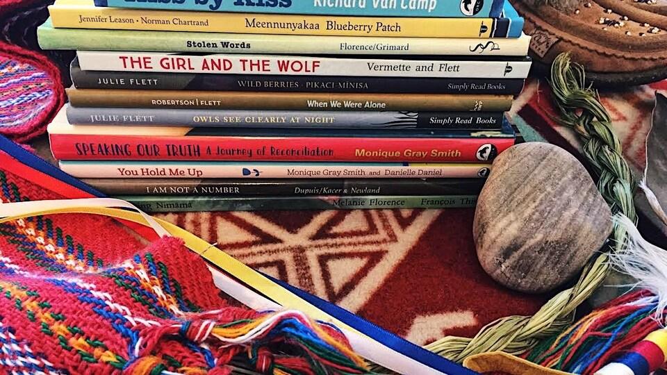 Une pile de livres à côté d'une tige de sauge.