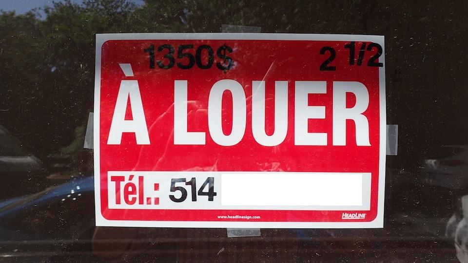 Affiche « À louer » collée dans une fenêtre.