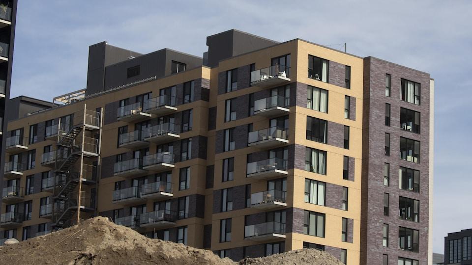 Un complexe de condos à Montréal, avec à l'avant-plan une butte de terre.