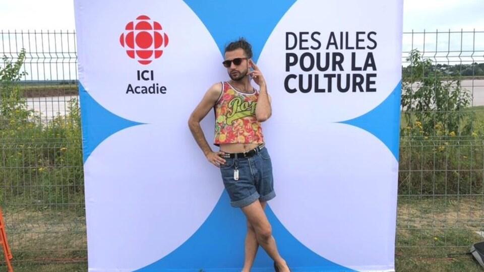 Xavier Gould pose devant un fond avec le libellé « ICI Acadie, des ailes pour la culture ».