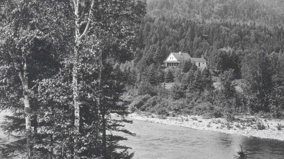Photo en noir et blanc de 1910 où l'on voit le camp de pêche, photographié à partir de l'autre rive de la rivière Cascapédia