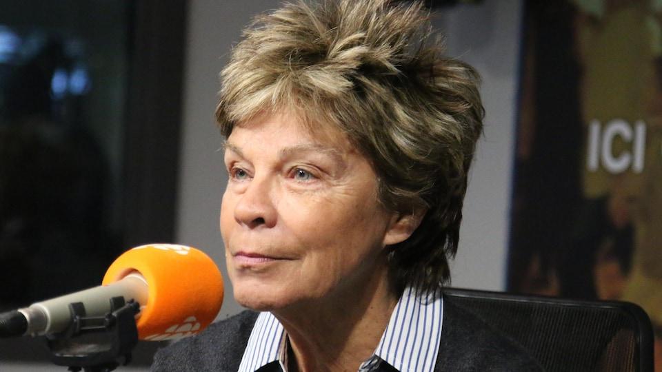 Madame Beaudoin parle au micro en studio radio.