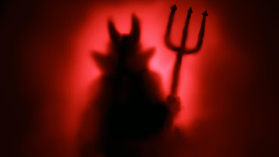 Dans la brume, une silhouette de Satan.
