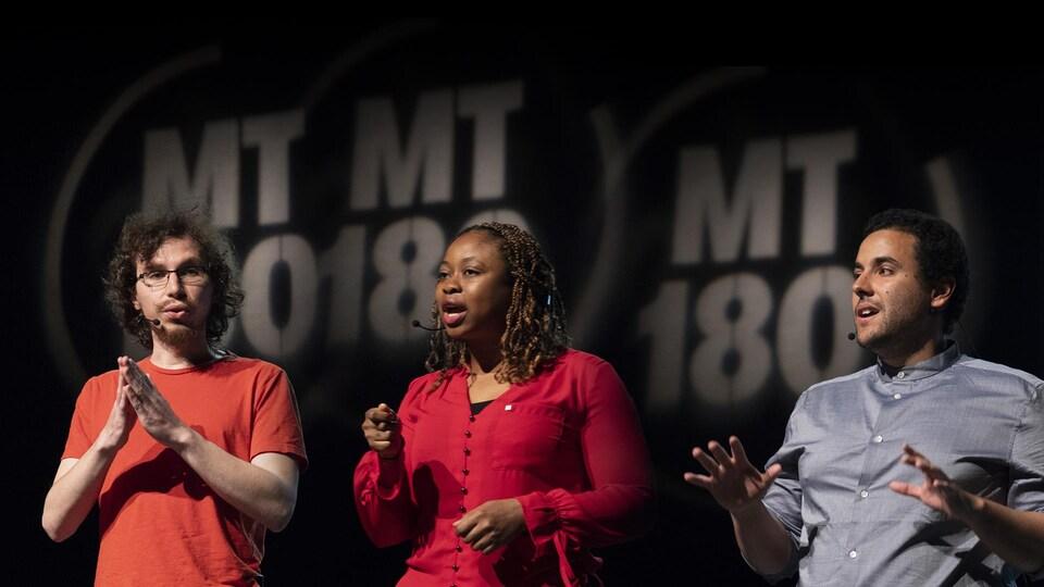 Deux jeunes hommes et une jeune femme sur une scène qui font une présentation