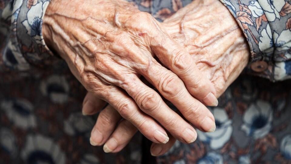 Deux mains ridées de femme.