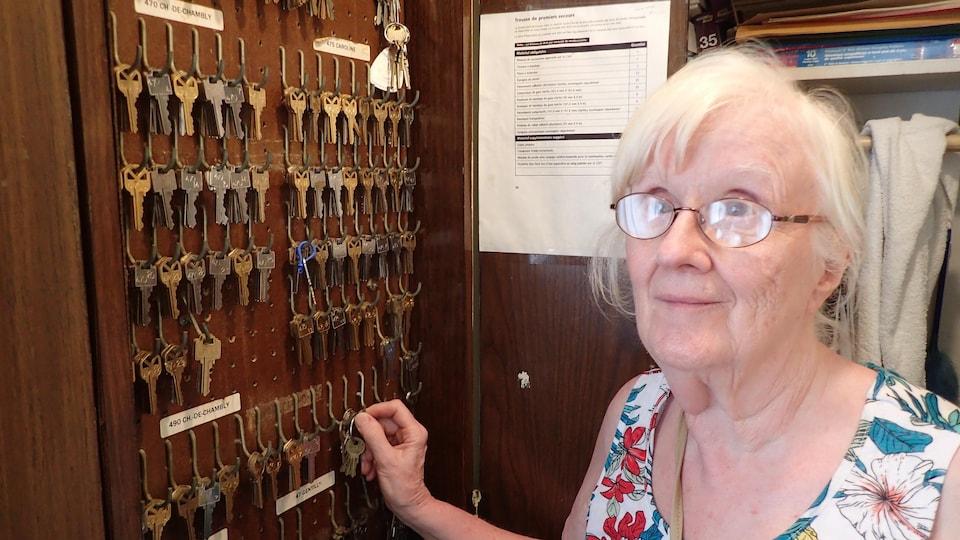 Une dame âgée à côté d'un présentoir sur lequel une multitude de clés sont accrochées.