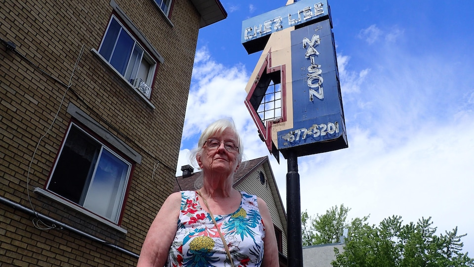 Une dame âgée devant un immeuble percé de fenêtres et un panneau lumineux disant « Chez Lise Maison ».