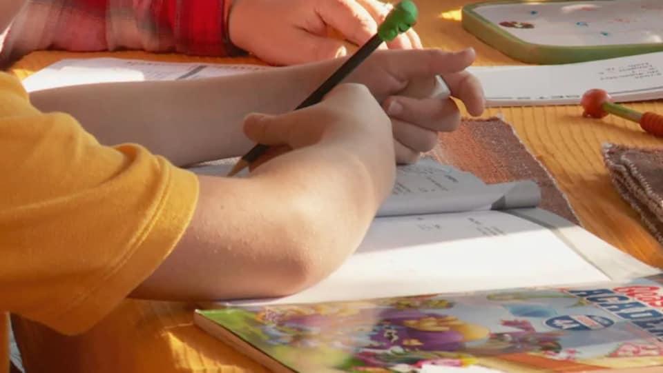 La main d'un enfant en train d'écrire dans un cahier d'école