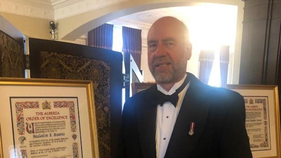 Un homme en kilt et en veston debout à côté d'un document officiel encadré