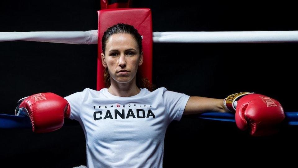 Une femme assise dans le coin d'un ring de boxe regarde la caméra.