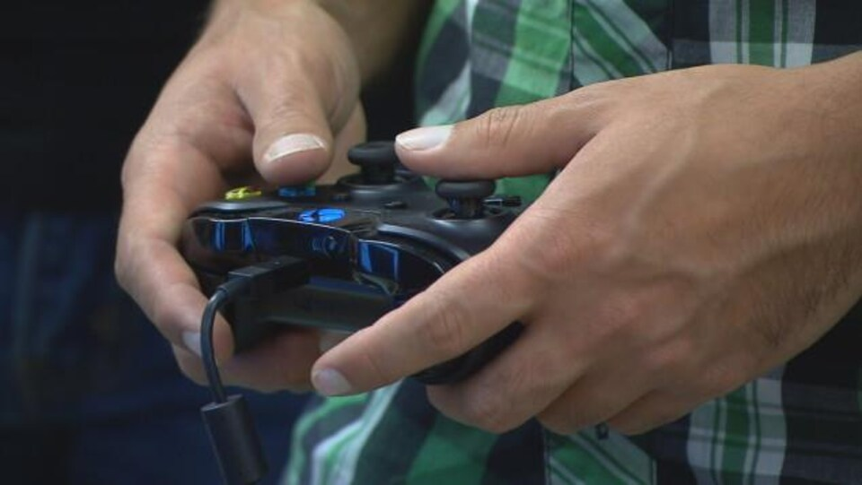 Un joueur de jeux vidéo tient une manette.