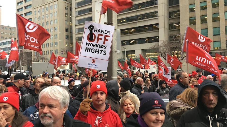 Des manifestants entre des édifices du centre-ville de Toronto tiennent haut dans les airs des drapeaux avec le symbole d'Unifor et des slogans syndicaux sur ceux-ci.