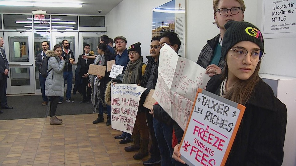 Plan large d'étudiants alignés sur le mur de l'entrée des bureaux de l'administration tenant des pancartes qui dénoncent les compressions budgétaires et les hausses de frais de scolarité.