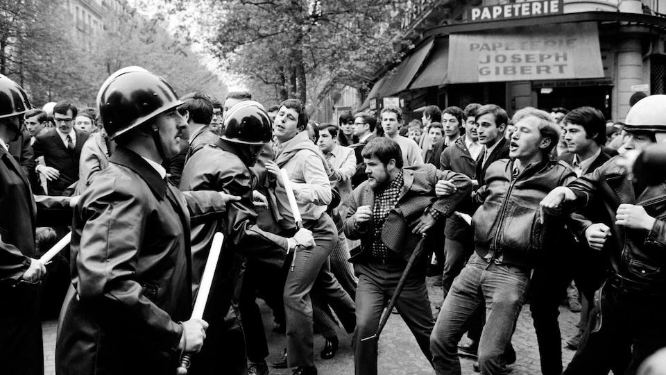 Image en noir et blanc d'une scène de rue où l'on sent la tension entre les deux groupes. Plusieurs hommes sont visibles. Des policiers tiennent des matraques.