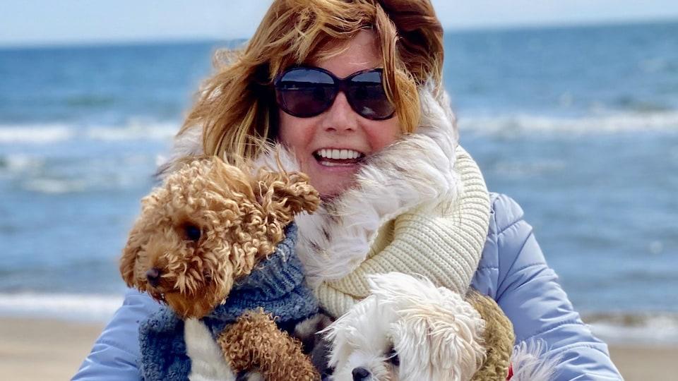 Manon Charbonneau sur le bord de la mer avec deux chiens.