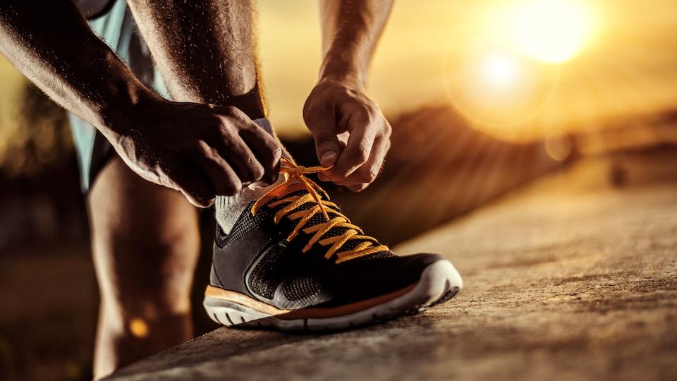 Un homme se prépare pour une course à pied en attachant les lacets de son soulier.