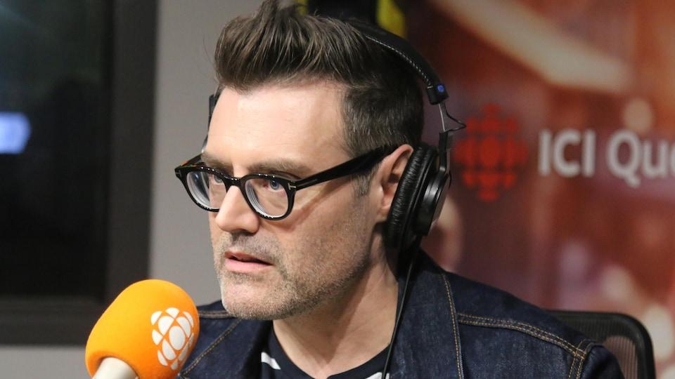 Un homme parle au micro en studio radio.