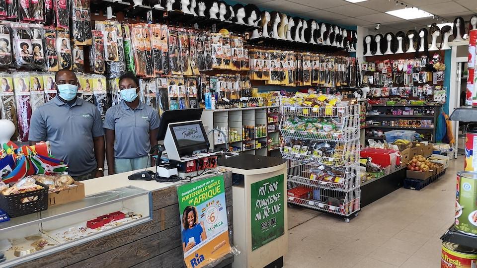 Jean Ngoube et sa fille sont à la caisse du Marché Tropical de Sudbury, entouré par des produits tropicaux, des extensions et des perruques.