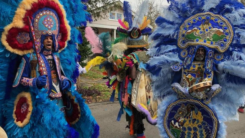 Des gens vêtus de costumes traditionnels sont dans la rue pour le défilé.