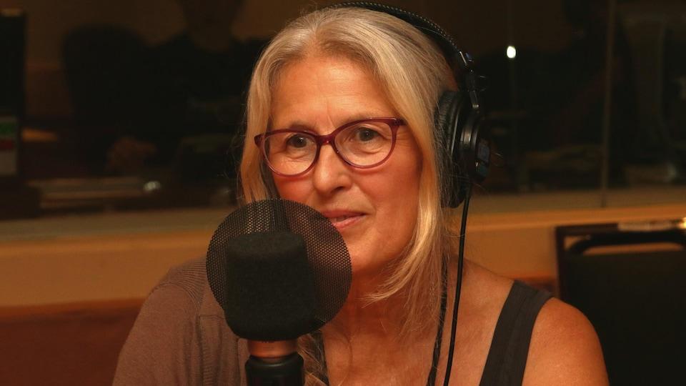 Margie Gillis devant un micro de radio et un casque d'écoute sur la tête dans un studio de radio.