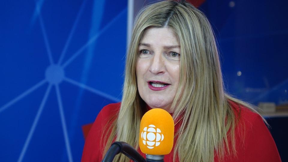 Marie-France Bazzo derrière un micro dans un studio radio de Radio-Canada