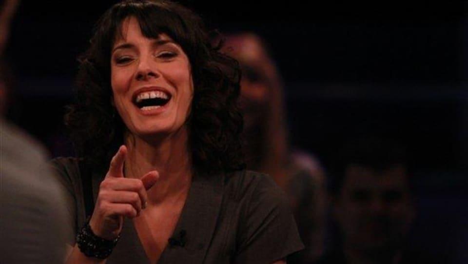 La femme est en face de quelqu'un non identifié, elle le pointe du doigt en éclatant de rire.