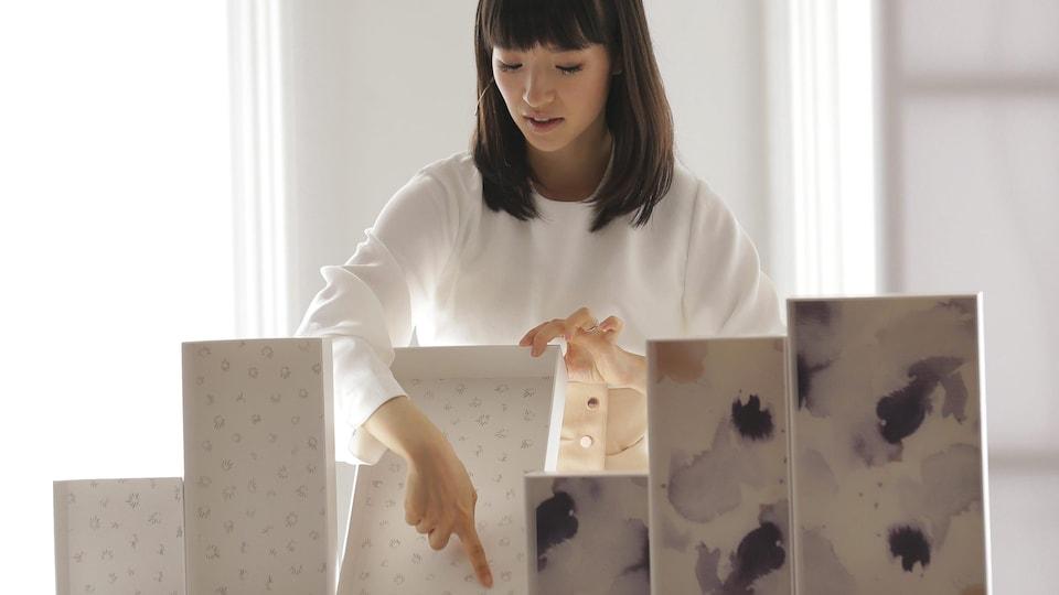 Une femme se tient debout devant une table sur laquelle sont posées six boites de carton. Elle pointe l'intérieur de l'une de celle-ci.