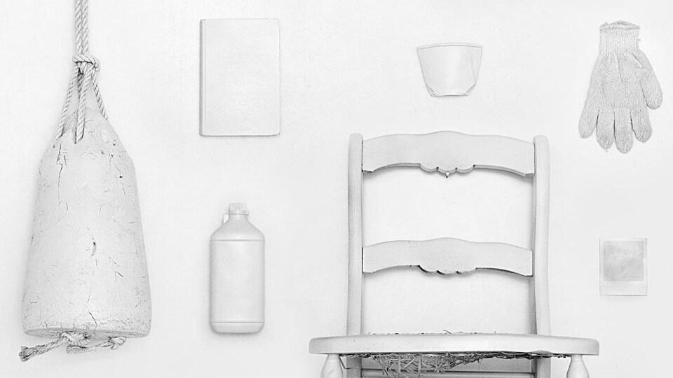 Une bouée, une chaise, un gant et d'autres objets tous peinturés en blanc.