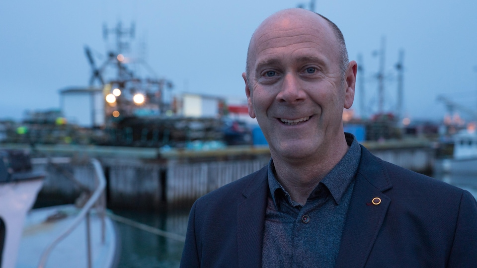 Mario Cyr, photographe sous-marin, sourit devant un port.