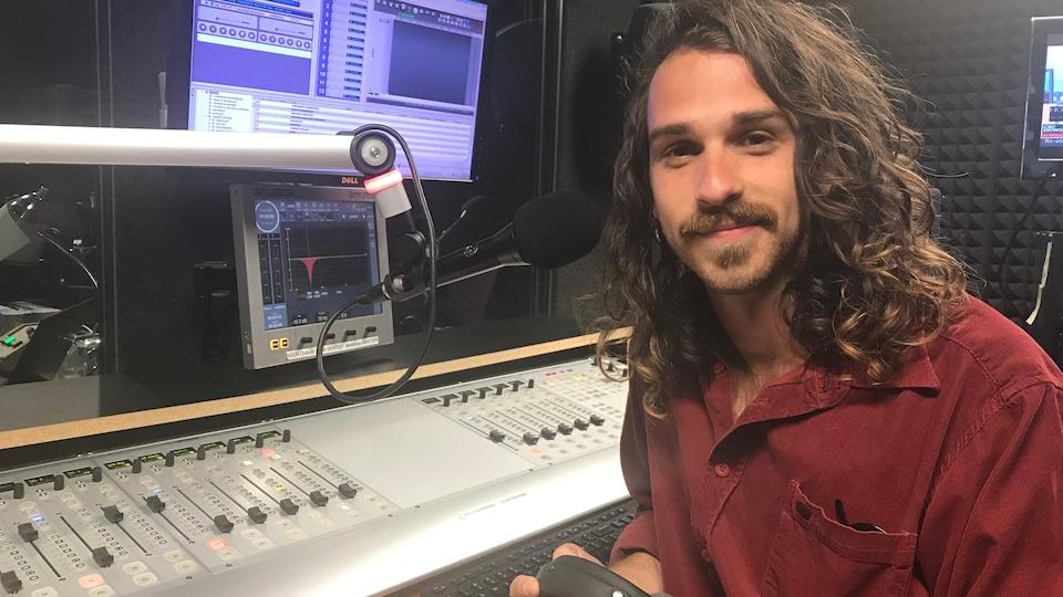 Jeune hippie accoudé à une console sonore