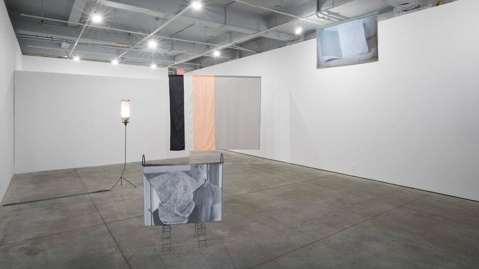 Une toile est présentée sur un présentoire dans une grande salle avec comme seul autre objet, une lampe sur pied.
