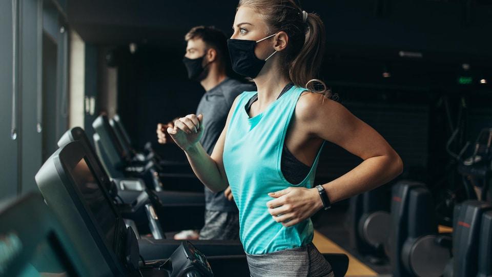Des gens dans un gym courent sur un tapis roulant tout en portant un masque et en gardant leur distance.