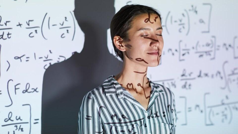 Une femme, les yeux fermés, contre un tableau blanc sur lequel sont projetées des formules mathématiques.