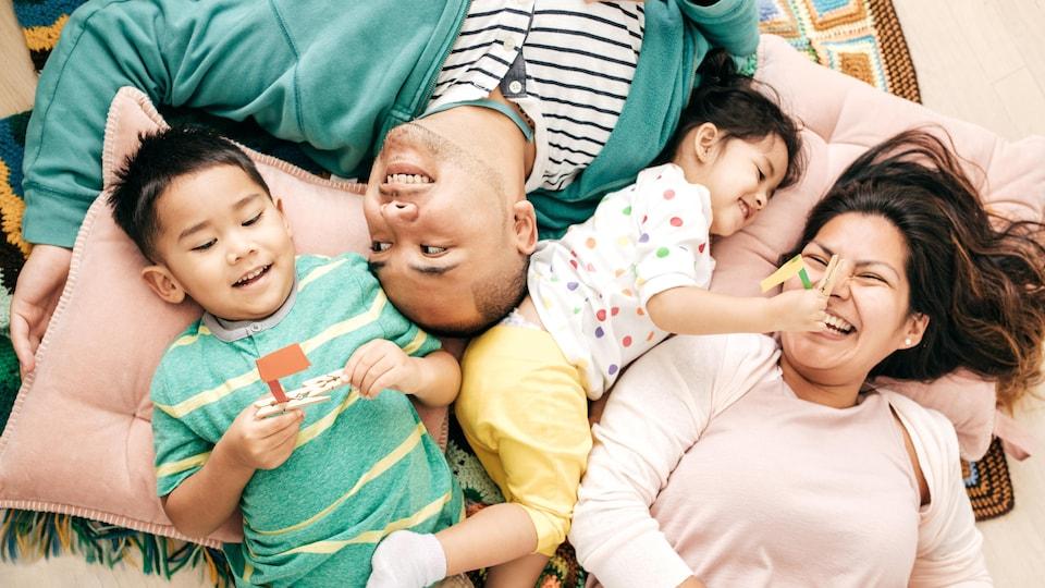 Famille entrain de rire, allongée sur des coussins
