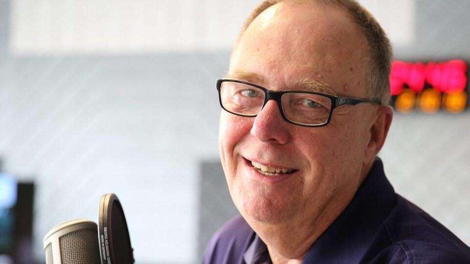 Le journaliste Robert McMillan pose derrière un micro.