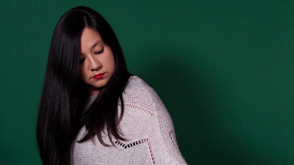 Portrait de l'artiste sur fond vert. Elle porte un chandail beige, elle a la tête penchée et regarde vers le bas.