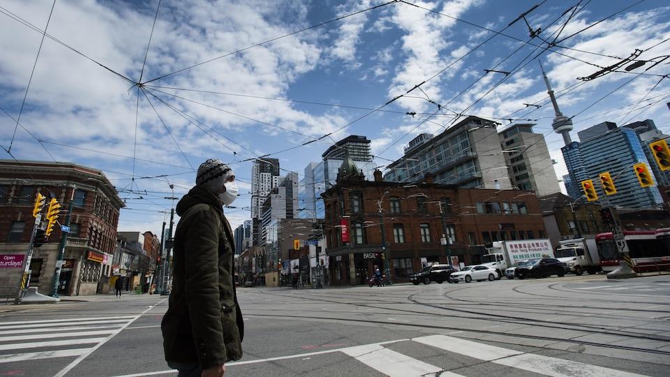 Un homme qui porte un masque traverse une rue de Toronto.