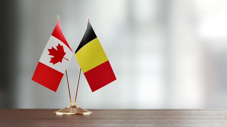 Un drapeau canadien et un drapeau belge sur un socle, sur une table.