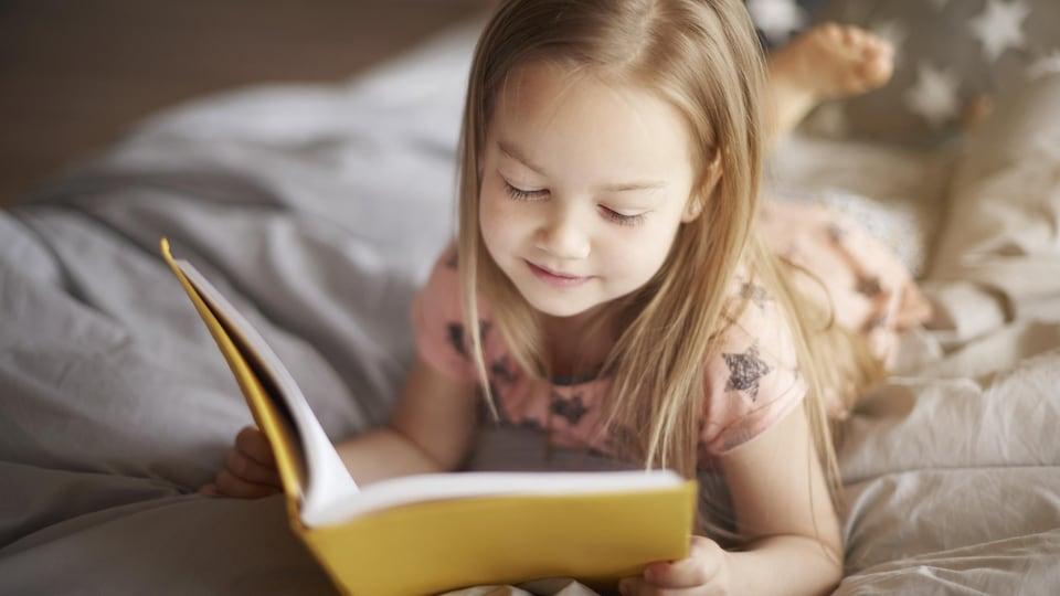 Une petite fille lit un livre allongée sur un lit.
