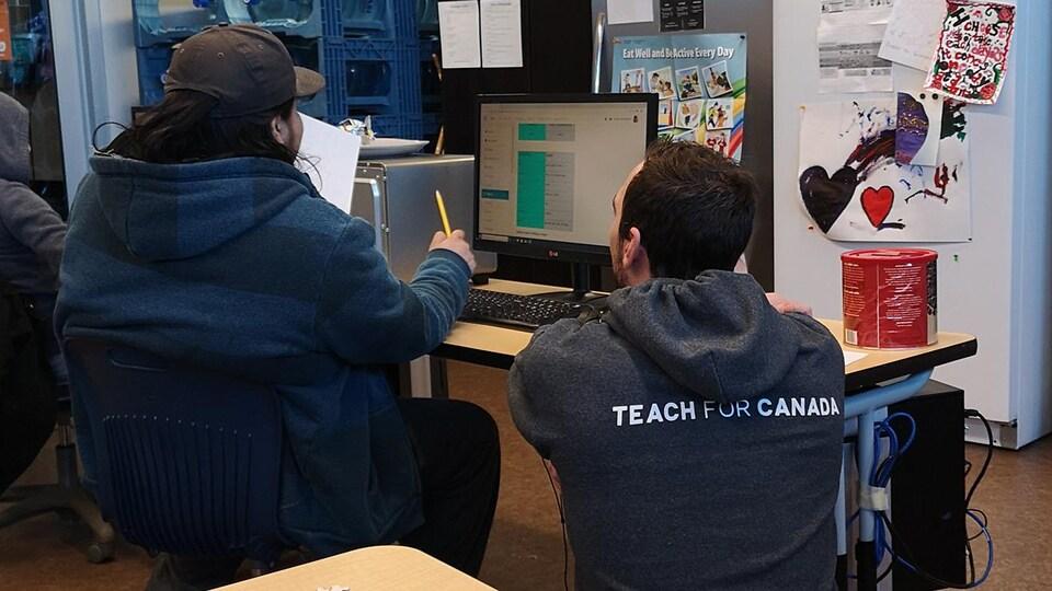 Un enseignant aide un élève