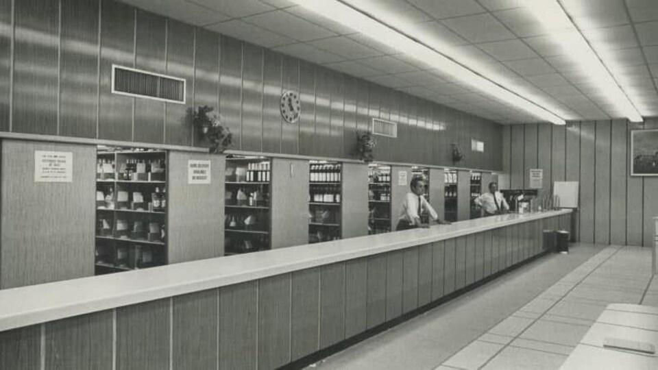 Une succursale du LCBO en 1971. Deux hommes sont debout derrière le comptoir des commandes.