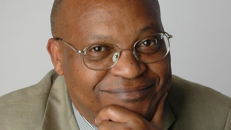 Un homme à lunettes sourit en se tenant le menton avec la main.