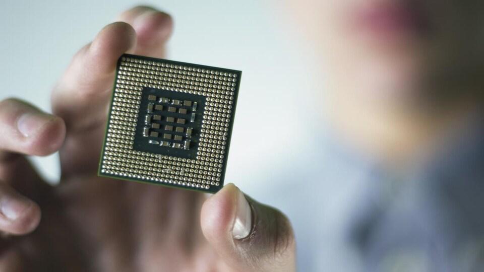 Une main qui tient un microprocesseur.