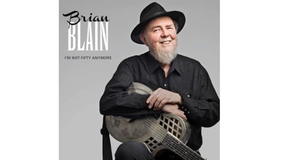 Couverture de l'album. Brian Blain est assis souriant, il porte un chapeau noir et tient une guitare métallique.