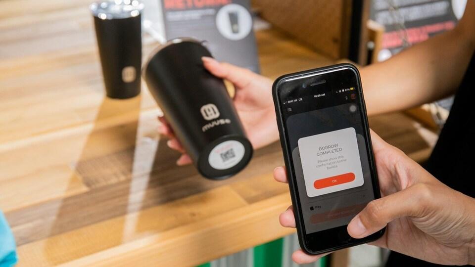 Une personne utilise un téléphone intelligent pour emprunter une tasse réutilisable. Des tasses réutilisables marquées « Muuse » se trouvent en arrière plan.